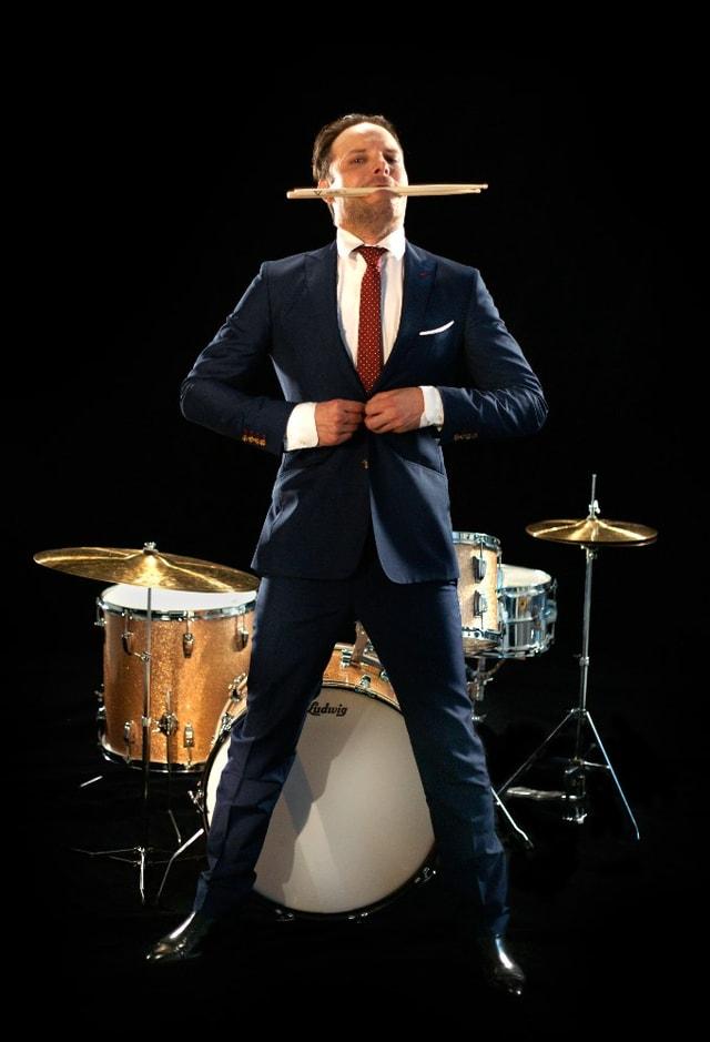 Dominik Deville posiert vor einem Schlagzeug mit den Schlagzeugsticks im Mund