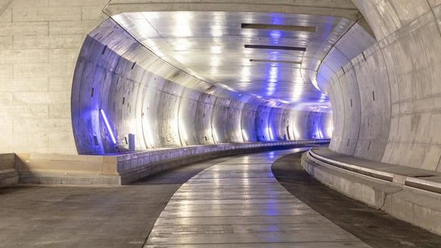 Der Blick in einen Tunnel, der eine rechtskurve macht. Viel glänzender Beton und blauer Schimmer an den Wänden.