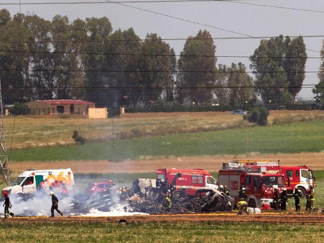Trümmer eines Flugzeugs auf einem Feld, daneben Feuerwehrautos.