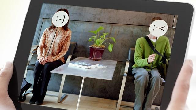 Ein IPad, darauf ein Bild von zwei Menschen, die sich ein Karton mit einem Smiley drauf vors Gesicht halten.