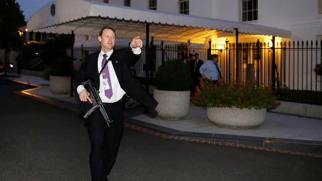 Ein Sicherheitsbeamter mit einer Waffe. Er ist sichtlich in Aufregung.