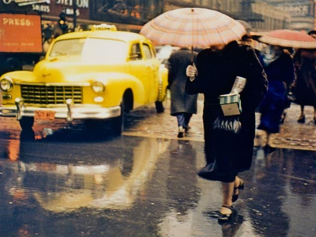 Eine Frau mit einem Schirm über dem Gesicht läuft im Regen vor einem gelben Taxi durch.