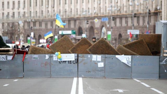 Demonstranten stehen hinter einer Barrikade auf einer Strasse