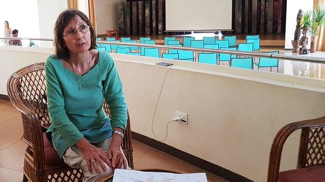 Eine Frau sitzt in einem Konferenzraum.