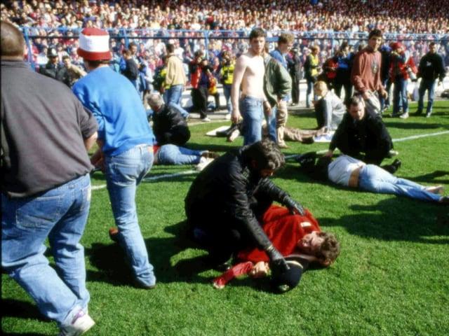 Fans auf dem Spielfeld neben Toten und Verletzten.