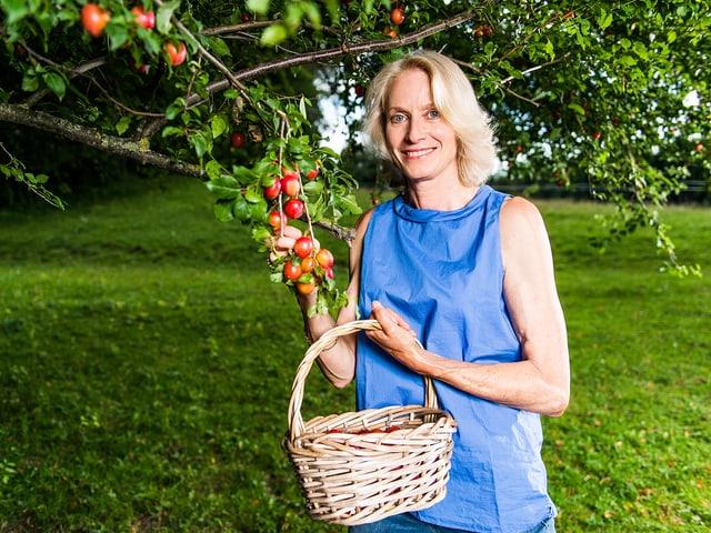 Béatrice bei einem Apfelbaum.
