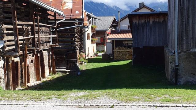 Blick zwischen die Häuser in Vella. Auf dem Boden Gras statt Asphalt.