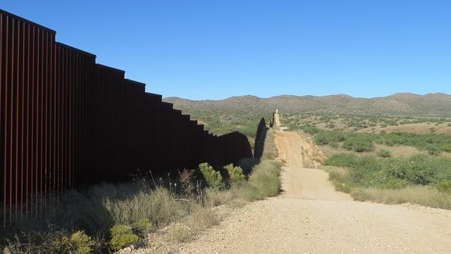 Links Grenzzaun, rechts eine gerade, staubige Strasse.