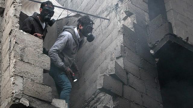 Syrien: Zwei Zivilisten suchen in einem Gebäude in Aleppo nach Überlebenden. Zuvor wurden sie von Regierungstruppen angegriffen.