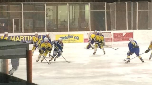 giugaders da hockey en tenues mellens e blaus dattan sin il glatsch a Ludains, San Murezzan