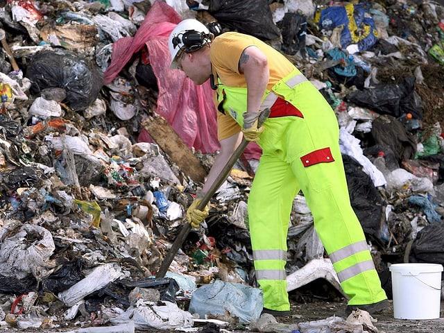 Zu sehen ist ein Arbeiter auf einer Müllhalde.
