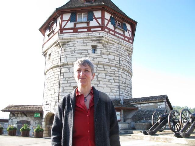 Eine Frau mit kurzen, grauen Haaren vor einem historischen Turm.