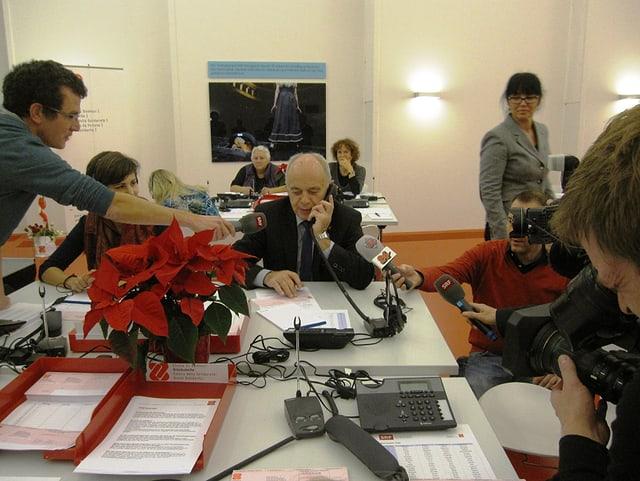 Bundespräsident Ueli Maurer spricht am Telefon unter Beobachtung von Medienschaffenden.