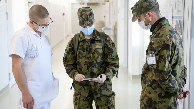 Zwei Soldaten und ein Arzt im Gespräch
