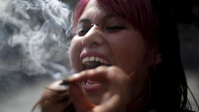 Eine Frau hält einen Joint in der Hand, den Mund weit geöffnet.