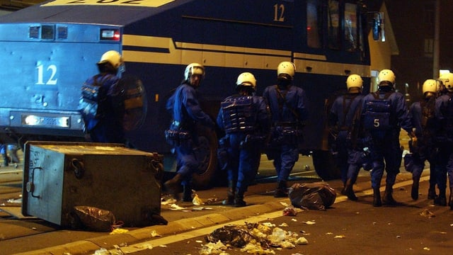 Uniformierte Polizisten stehen vor einem Wasserwerfer.