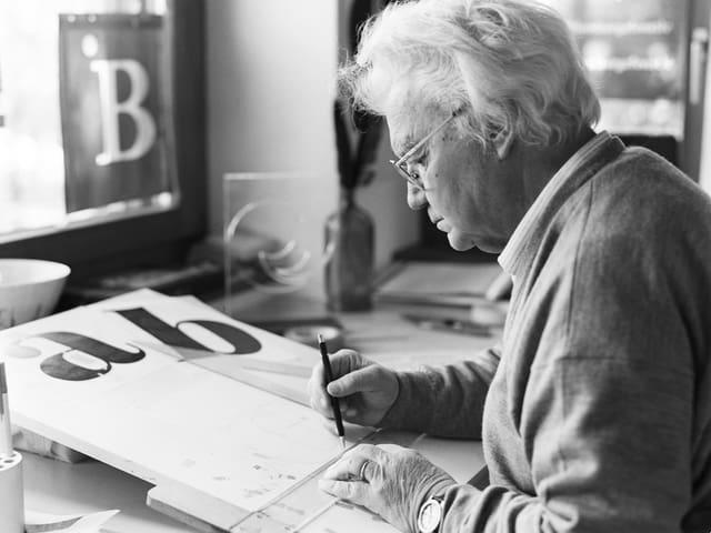 Adrian Frutiger, an einem Tisch sitzend, an einer Schrift arbeitend.
