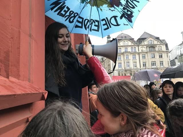 Eine junge Frau mit Megaphon und Schirm.