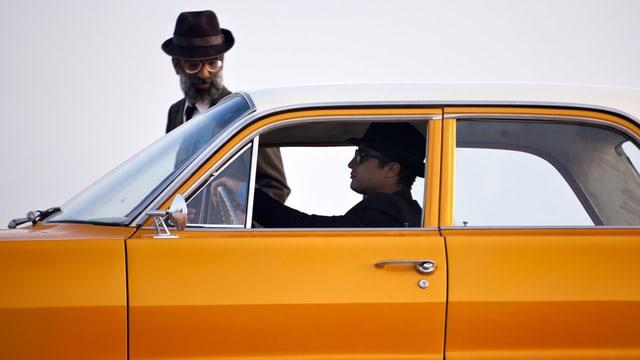 Ein Mann in einem orangen Auto. Neben dem Auto geht ein Mann mit Hut.