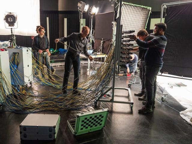 Der Rahmen mit den 64 Kameras (die Lichtfeld-Kamera) auf einem grösseren Rahmen mit Rädern, vier Wissenschaftler, die das ganze verkabeln.