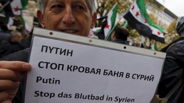 """Mann hält ein A-Blatt hoch mit der Botschaft """"Putin, stopp das Blutbad in Syrien"""" in verschiedenen Sprachen"""