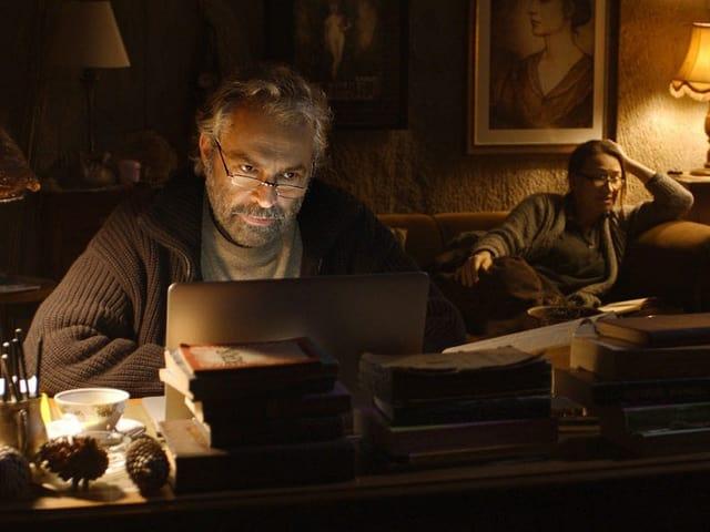 Hauptfigur Aydin in der Schreibstube mit seiner garstigen Schwester Necla im Hintergrund.