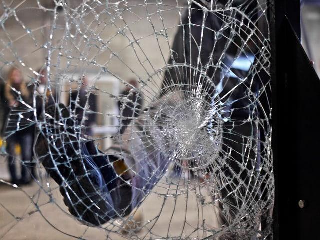 Hinter einer zerschlagenen Fensterscheibe ist eine Silhouette zu sehen.