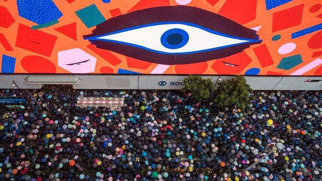 Ein grosses Auge an einer Wand. Vor der Wand sind viele Protestierende.