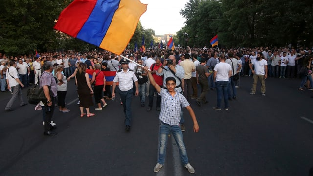 Ein Demonstrant schwingt die armenische Fahne, im Hintergrund ist ein Protestzug zu sehen.