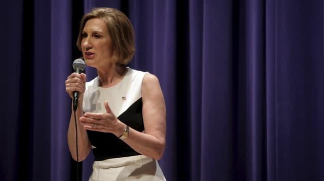 Carly Fiorina in einem ärmellosen Kleid, stehend mit einem Mikrofon, vor einem blauen Vorhang.