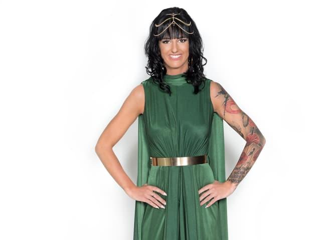 weisser Hintergrund, dunkle Haare, grünes Kleid, linker Arm tätoviert