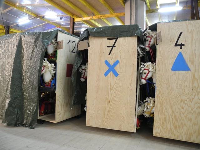 IN Kisten hinter der Bühne lagern Kostüme und Requisiten in Kisten.