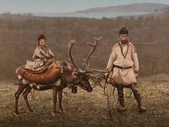 Ein Altes Foto: Ein Mann in traditioneller Kleidung hält ein Rentier, auf dem ein Kind sitzt.