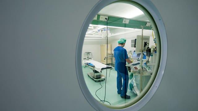 Blick durch ein Fenster in einen Operationssaal. Drinnen sieht man einen Arzt, an einem Computer stehens.