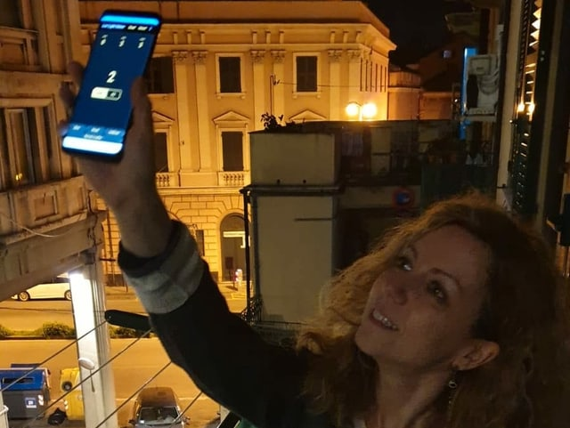 Frau in Italien hält Handy aus dem Fenster, um Lichtstrahlung zu messen.