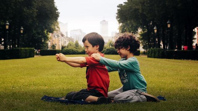 zwei jungs sitzen im gras