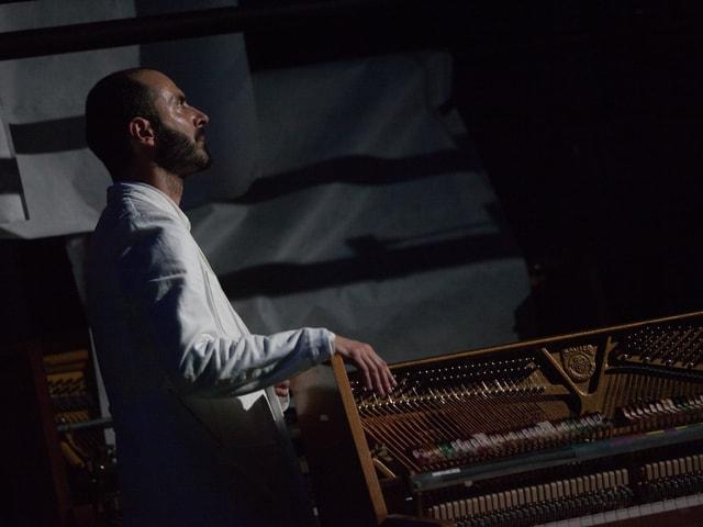 Mann sitzt im Dunkeln und schaut nach oben. Die hand hält er auf ein offenes Cembalo.