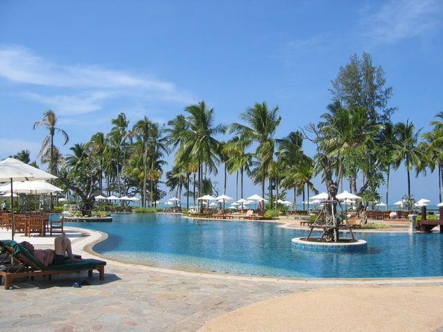 Eine Hotelanlage mit Swimmingpool und Palmen