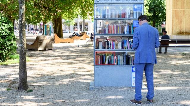 Ein Mann steht in einem Park vor einem Bücherregal.