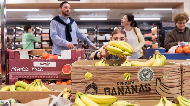 Einkaufszene in einem Supermarkt in der Früchteabteilung, mehrere Kunden sind zu sehen.