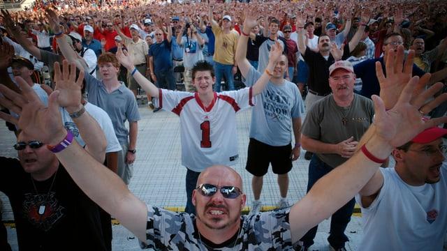 Tausende Menschen strecken die Hände in die Höhe und haben etwas krampfhaft-verbissene Gesichter.