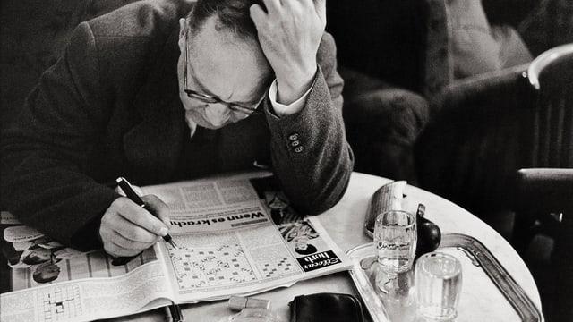 Ein älterer Herr löst an einem Tisch sitzend ein Kreuzworträtsel in einer Illustrierten (s/w).