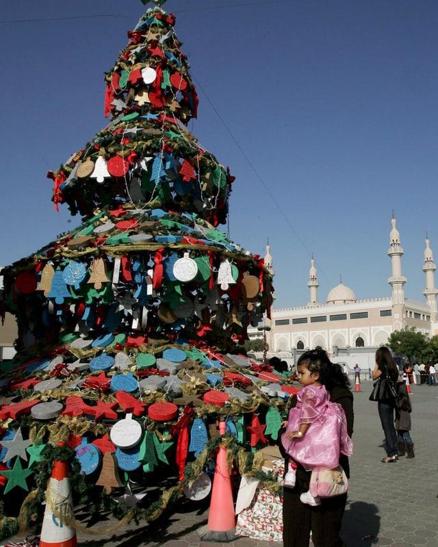 Ein bunter Weihnachtsbaum steht auf einem öffentlichen Platz in Dubai. Eine Frau mit einem Kind laufen daran vorbei.