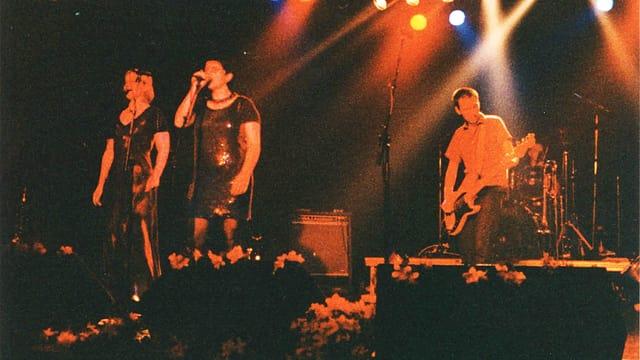 Konzertbühne mit zwei Sängerinnen und einem Bassisten. Alles in rotem Licht