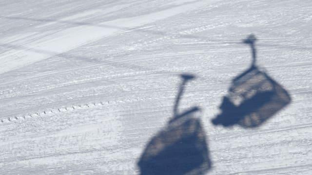 Blick auf eine Piste mit den Schatten einer Seilbahn.