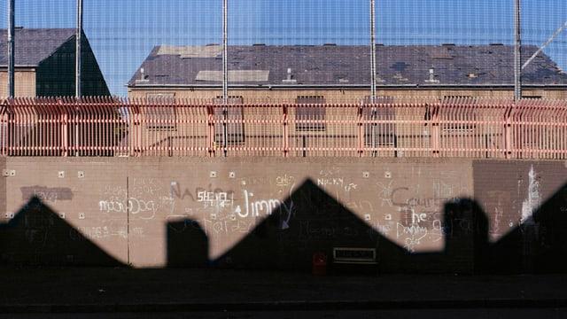 Eine Mauer, im Hintergrund ein Backsteinhaus