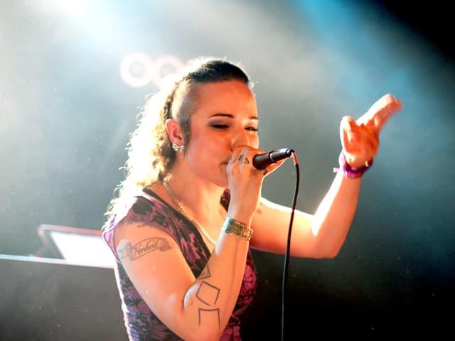 Eine junge Frau mit Tätowierungen und ärmellosem Top hält sich ein Mikrofon an den Mund und steht auf einer Bühne im Scheinwerferlicht.