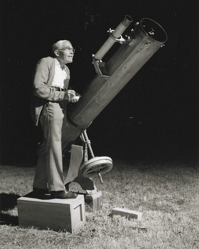 Clyde Tombaugh schaut in ein Teleskop.