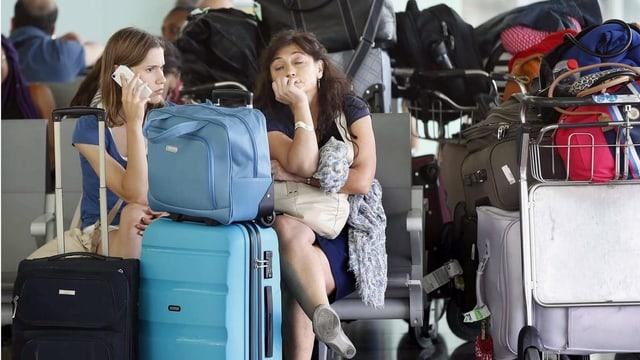 Zwei Frauen warten mit Gepäck am Flughafen.