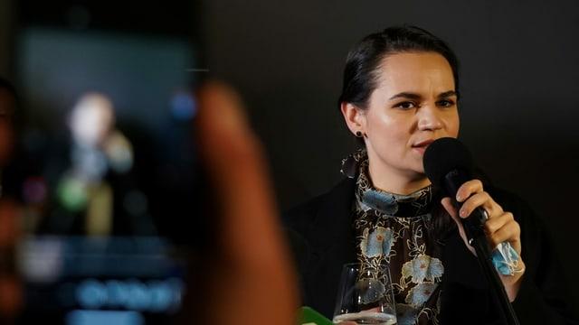 Tichanowskaja spricht in ein Mikrofon und wird von einem Handy aufgezeichnet.